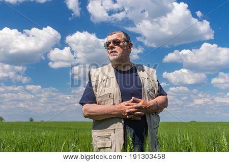 Portrait of senior farmer standing inside unripe crops against blue cloudy sky