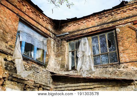 Broken windows with polyethylene film instead of glasses on the old abandoned brick building in Kiev Ukraine