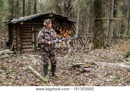 Male hunter near a hunting lodge in forest