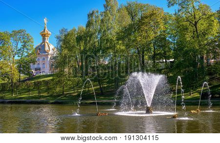 Petergof, Russia - June 5, 2017: View of the building Special pantry from the Sand Pond. The dome has gilding. In the center of the pond there is a fountain.