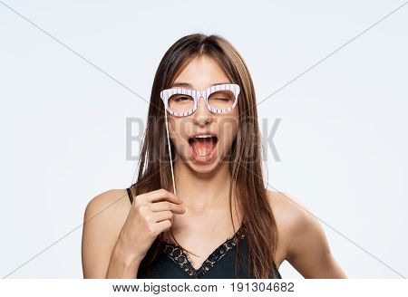 A conceited woman with glasses on a light background.