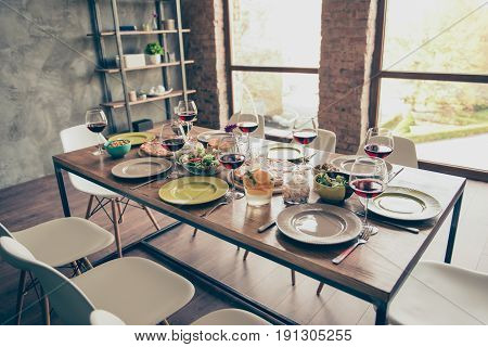 All is ready! Generously served wooden table with yummy fresh dishes and glasses of red wine are ready for the family lunch at loft designed dining room