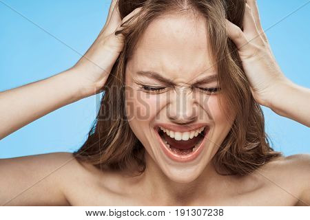 Woman screams, woman holds on to head on blue background portrait.