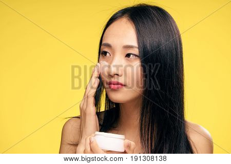 Woman applying cream on face, face care, woman holding cream on yellow background.