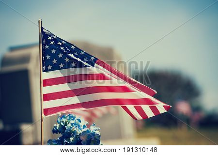 American veteran flag waving in the wind in the cemetery