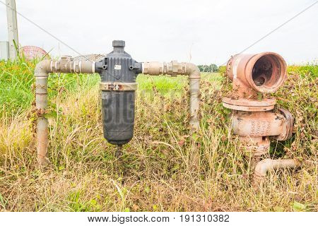 Abandoned Rustic Water Pipe and Water Filter in Rural Field as Plumbing in Agroindustry Concept