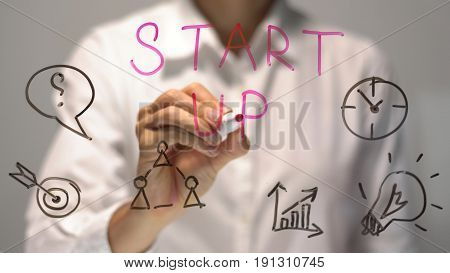 Start Up concept. Woman writing and drawing on transparent screen. Businesswoman write on board.