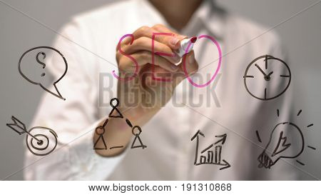 Woman writing SEO on transparent screen. Businesswoman write on board. Drawing on desk.