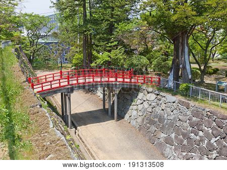 MARIOKA JAPAN - MAY 22 2017: Red bridge over the moat between main (honmaru) and second (ninomaru) baileys of former Marioka castle Japan. Castle was constructed in 1633 and dismantled in 1874