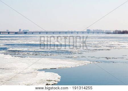 The spring ice drift on the river Volga. Road bridge in the city of Saratov. Russia. A Sunny day in March. Blue sky.