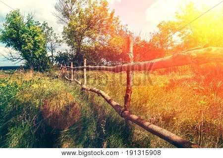 Wooden fence in a village at sunset. Colorful scenic background