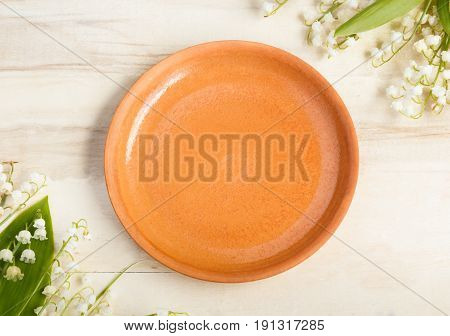 Empty ceramic plate on wooden background. Bouquet of flowers lilies of the valley. Copy space.