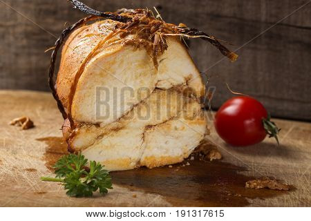 Close up of homemade juicy chicken pastrami on wooden background