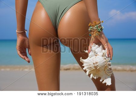 Sporty back of a beautiful woman in bikini with a seashell in her hands on sea background. Sexy buttocks