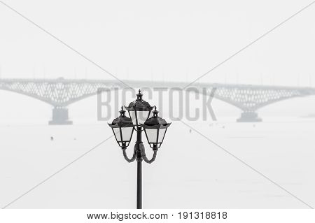 Street lamp on the background of the bridge across the Volga. Winter day, Saratov, Russia