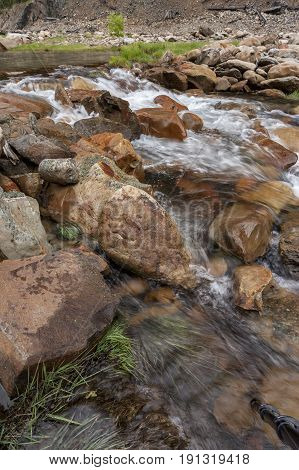 Water flows over rocks and grass. Large rocks in Canyon Creek a few miles from Wallace Idaho.