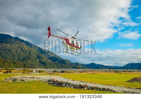 SOUTH ISLAND, NEW ZEALAND- MAY 25, 2017: A helicopter lifting off ready to take tourists to a glacier in the South Island of New Zealan.