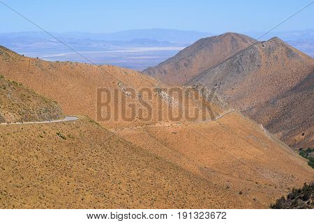 Road traversing up a barren dry mountain ridge with the Mojave Desert beyond taken in the Southern Sierra Nevada Mountains, CA