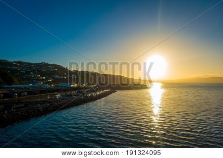 SOUTH ISLAND, NEW ZEALAND- MAY 25, 2017: Gorgeous coast zone of the city in the horizont from ferry between two inslands, in a sunset in New Zealand.