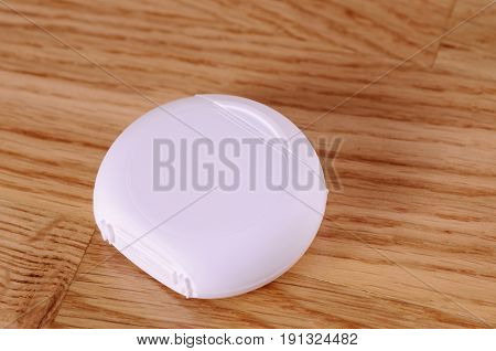 A pack of dental floss on wooden background.