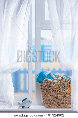 Beach basket filled with towels for the beach sitting in an open window