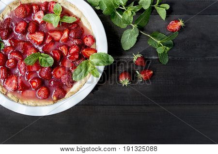 Strawberry pie on a brown wooden table with mint