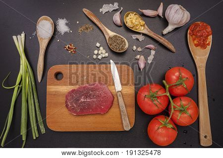 Raw steak and vegetables and spices used in cooking.