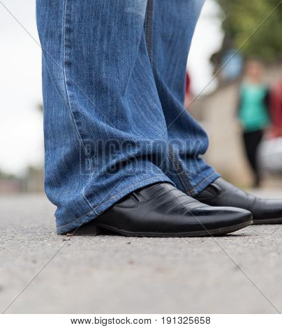 male legs in jeans and shoes . A photo
