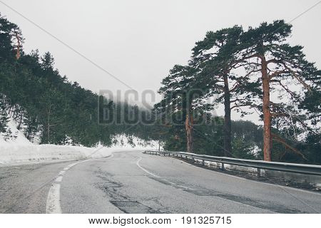 High mountain road. Mountain road landscape covered with snow.  Beautiful view of mountain road in the forest covered with snow. Mountains of Navacerrada.