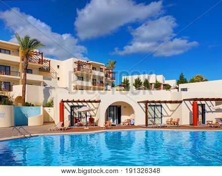 RHODES ISLAND, GREECE, JUN 19, 2005: View on swimming pool and tourists in hotel Miraluna Kiotari Bay. Traditional Greek hotel architecture. Rectilinear architecture. Famous Greece vacations tours.