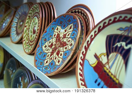 RODOS ISLAND, GREECE, JUNE 22, 2013: View on hand made painted classical traditional greek plaques plates dishes at workshop. Famous Greece miths and mythology paitings. Traditional Greece souvenirs