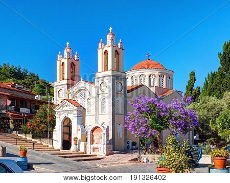 RHODES ISLAND, GREECE, JUN 22, 2015: Beautiful traditional beige orange colors Greek church Agiou Panteleimonos among green hills violet trees, red flowers. Famous Greece islands vacations tours