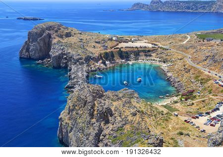 Beautiful view on ancient coral stone rocks and white yachts boats in Lindos blue sea bay on Greece island Rhodes. Greece islands holidays vacation sightseeing points tours travel trip