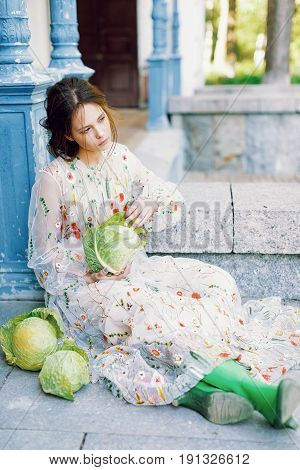 Beautiful girl sitting near the house with many cabbages and lokking aside. Fashion portrait of pretty girl with cabbage. Girl and cabbages. Cute girl in cabbage.