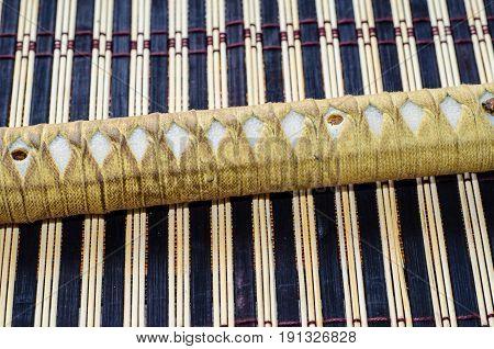 Handle Of The Japanese Sword Katana On Bamboo Mat