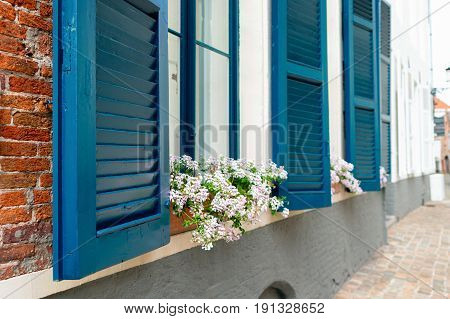 Window with a blue sun blind. A window on the first floor a sun blind is open on a window sill a box with flowers. The site of a wall from a red brick and a pavement from a stone blocks is visible