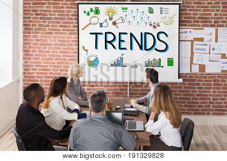 Businesspeople Looking At Trends Presentation On Projector In Business Meeting