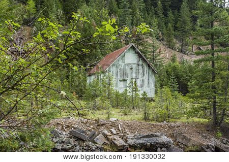 An old barn stands by a hill near Wallace Idaho.
