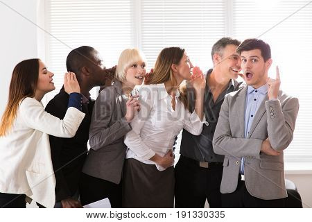 Business Colleague Whispering Secret Gossip To An Amazed Shocked Man With Wide Open Mouth