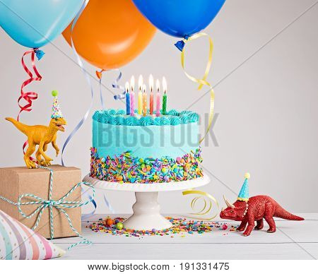Childs birthday party scene with blue cake gift box toy dinosaurs hats and colorful balloons over light grey.