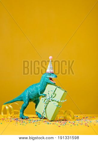 Toy dinosaur with birthday gift wearing a party hat on a yellow background.