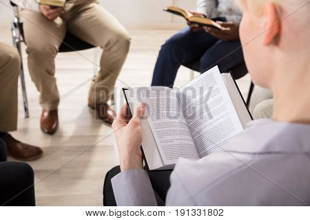 Close-up Of A Woman Reading Bible In Group