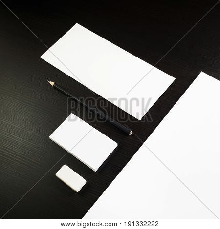Photo of blank stationery set on black wooden table background. Corporate identity template for ID. Responsive design mockup.