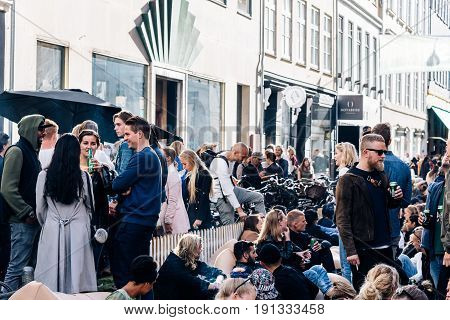 Copenhagen Denmark - August 11 2016. Crowd of young people sitting and enjoying in Kronprinsensgade a street in the Old Town of Copenhagen Denmark. Sunny day of summer