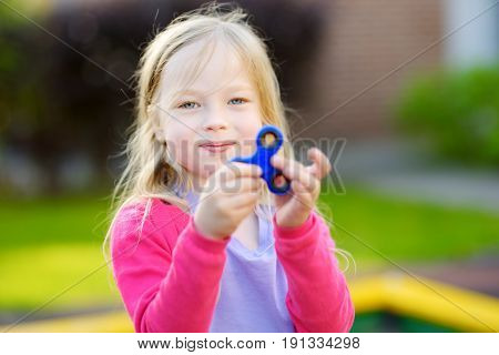 Cute School Girl Playing With Fidget Spinner On The Playground. Popular Stress-relieving Toy For Sch