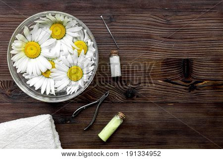 Spa composition on dark wooden desk with chamomile, towel and nippers copyspase top view.