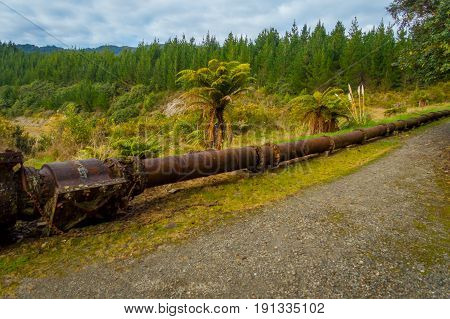 Stoned road with a rusted pipeline in one side of the road in south island, in New Zealand.