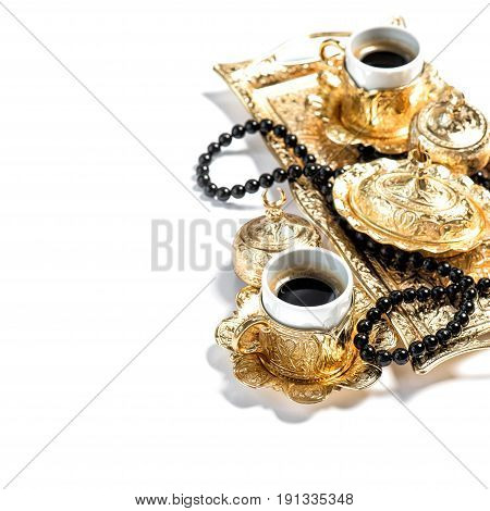 Golden coffee service and black rosary beads on white background. Ramadan kareem