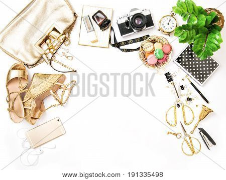 Feminine accessories bag shoes office supplies phone and green plant on white table background. Fashion flat lay sale shopping concept