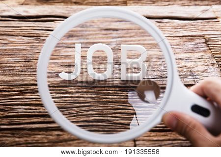 A Person Looking At White Job Word Through Magnifying Glass